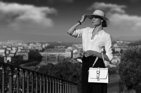 Stunning woman in a chic suit holds her hat against a Florentine background. Travel concept in Italy. Mixed media