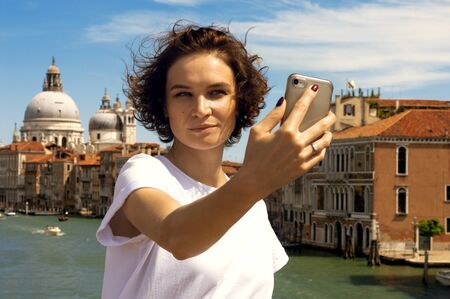 Charming girl takes a selfie on a bridge in Venice. Travel concept. Mixed media