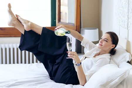 Charming girl lies on the bed in the room. She laughs and pours champagne into her glass. Hen-party. Mixed media Zdjęcie Seryjne