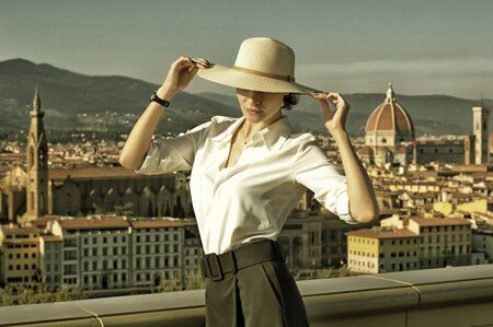 Delightful Italian woman stands on Piazzale Michelangelo in Florence with a beautiful view of the city. Mixed media