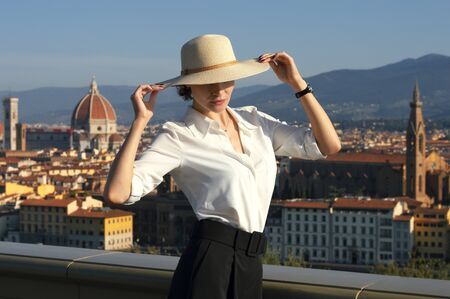 Charming Italian woman in a stylish suit enjoys the morning sun in Florence. Mixed media