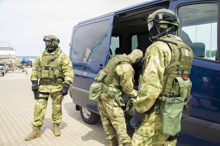 Special-purpose team arrived at the exercises. They unload weapons and special equipment from a minibus. The concept of defense, the Ministry of Defense, political instability, war. Mixed media