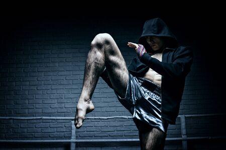 Boxeador tailandés en el ring golpea con una rodilla. El concepto de deportes, gimnasios, clubes de boxeo. Técnica mixta Foto de archivo