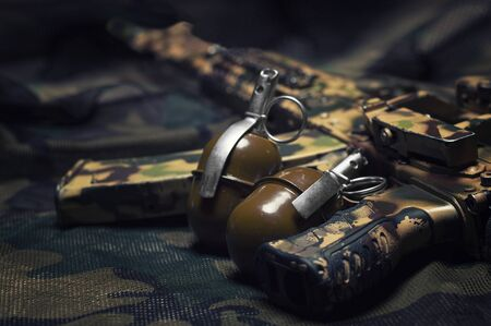 Two grenades lie on a camouflage background. The concept of military operations, political conflicts, armed forces. Top view. Mixed media