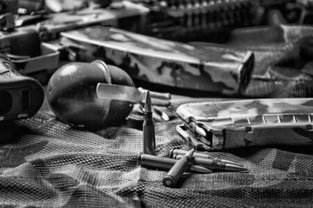 The concept of military ammunition. Cartridges for a machine gun, clip, grenade, machine gun. Background khaki. Mixed media Imagens