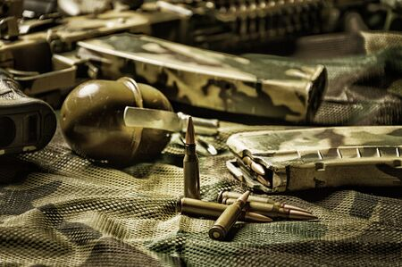 The concept of military ammunition. Cartridges for a machine gun, clip, grenade, machine gun. Background khaki. Mixed media