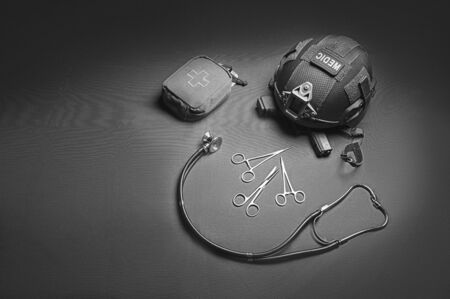 First aid kit, phonendoscope, a set of scissors with a helmet lie on a green background. View to the top. Military medicine concept Foto de archivo