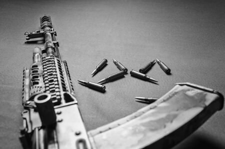 On a green background lies a camouflage machine gun along with bullets. View from above. The concept of war, political conflict. Mixed media Imagens