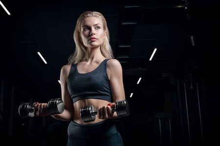 Charming sportswoman posing in the gym with dumbbells. The concept of bodybuilding, fitness, stretching, healthy eating. Mixed media