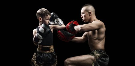 Thai boxing coach practicing punches with his student. Kickboxing concept, mma. Mixed media