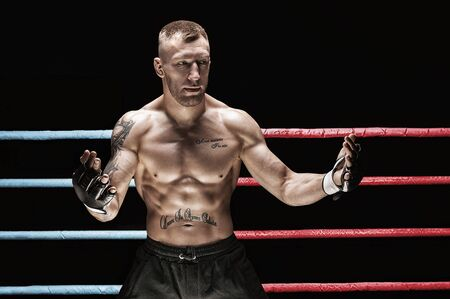 Mixed martial artist posing in boxing ring. Concept of mma, ufc, thai boxing, classic boxing. Mixed media