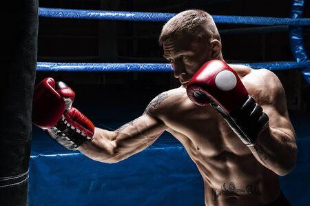 Kickboxer frappe le sac. Entraîner un athlète professionnel. Le concept de mma, lutte, muay thai. Technique mixte