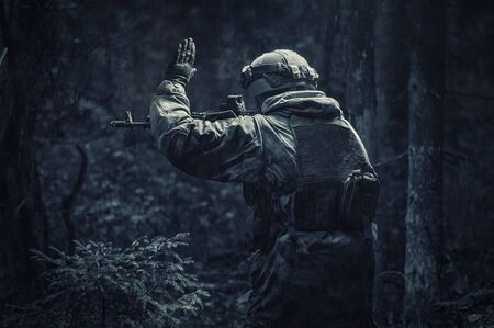 Portrait of a soldier walking through the forest. He raised his hand to warn his partner about the danger. Border Protection Concept. Back view Stock fotó