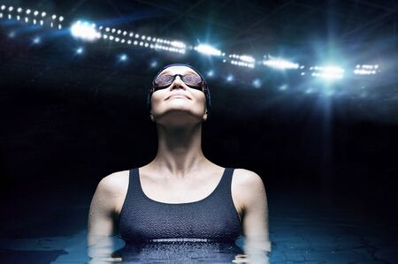 Charming woman posing in a pool against the backdrop of a stadium. Water sports concept. Front view. Mixed media Archivio Fotografico