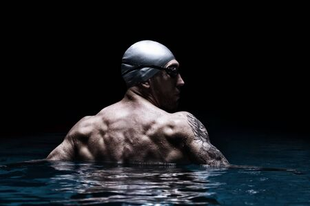 Portrait of a swimmer on a black background. The concept of swimming and water games. Back view. Mixed media