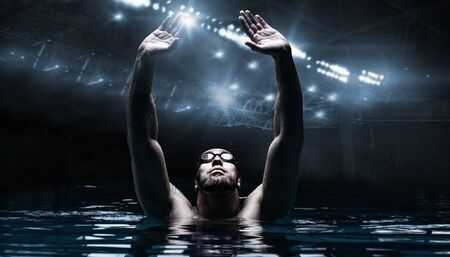 Swimmer in the pool raises his hands up. Water Sports Victory Concept. Arena with flashes. Mixed media