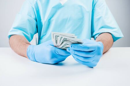 Doctor holds one hundred dollar bills. The concept of corruption in medicine. Mixed media Imagens