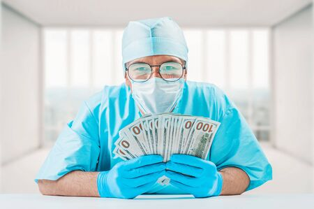 Portrait of a doctor holding hundred dollar bills. He is looking at the camera and smiling. The concept of corruption in medicine. Mixed media Imagens - 147824970