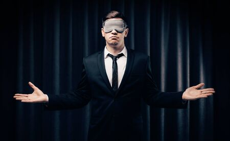 Portrait of a man in a mask for sleeping. He stands against the backdrop of a curtain. The concept of blind dates, dating on social networks. Mixed media Stock Photo