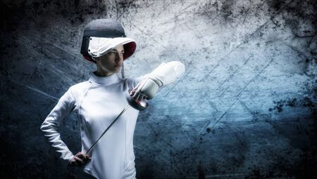 Charming girl dressed as a fencer posing with a mask and a sword. The concept of fencing. Mixed media