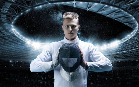 Portrait of a male fencer on the background of a sports arena. He holds a helmet in front of him. The concept of fencing. Mixed media Stock Photo