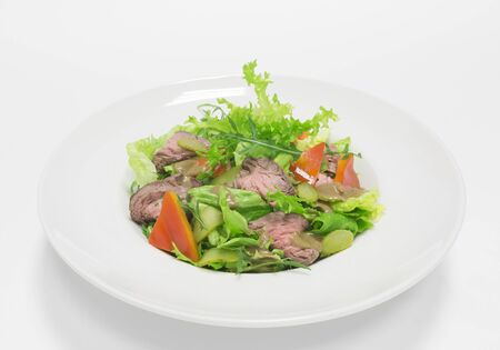 Gourmet salad with roast beef, pickled cucumbers and mustard. Top view. White background. Healthy eating concept. Mixed media 免版税图像
