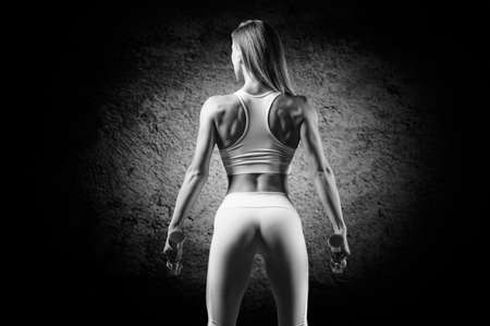 Adorable girl posing in the gym with dumbbells. Back view. The concept of bodybuilding, fitness, healthy lifestyle. Light spot. Mixed media
