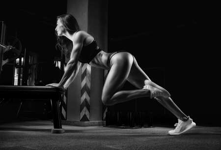 Beautiful girl trains in the gym on the bench. Sports, fitness and bodybuilding concept. Mixed media Imagens
