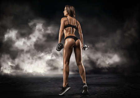 Tall adult woman with beautiful hair posing with dumbbells in her hand. Fitness and bodybuilding concept. Back view. Mixed media Standard-Bild