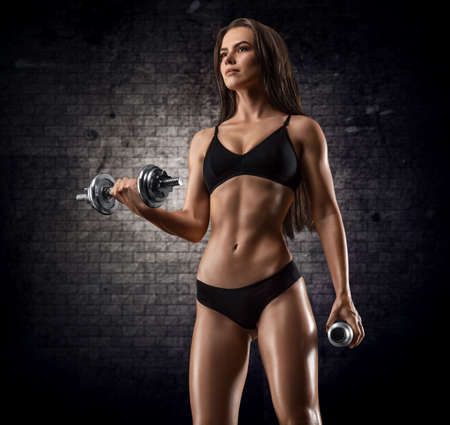 Tall adult woman with beautiful hair posing with dumbbells in her hand. Fitness and bodybuilding concept. Mixed media Standard-Bild