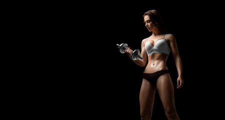Tall adult woman with beautiful hair posing with dumbbells in her hand. Fitness and bodybuilding concept. Mixed media 写真素材