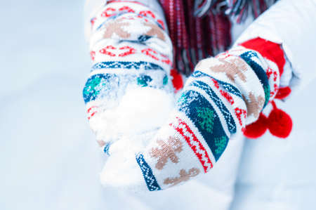 Image of a snowball in Christmas mittens. Concept for Christmas holidays and travel. Mixed media
