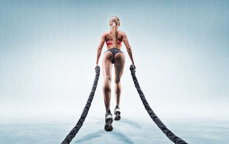Sports girl trains with ropes. Back view. The concept of sports, fitness, aerobics, bodybuilding, stretching. Mixed media