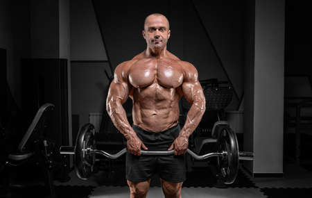 Professional weightlifter posing in the gym with a barbell in his hands. Classic bodybuilding. Mixed media