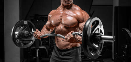 Powerful bodybuilder trains in a gym with a barbell. No name portrait. Bodybuilding concept. Mixed media Stock Photo