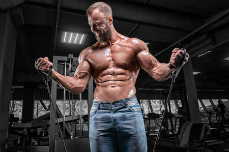 Professional athlete trains with elastic bands in the gym. Bodybuilding and fitness concept. Mixed media Фото со стока