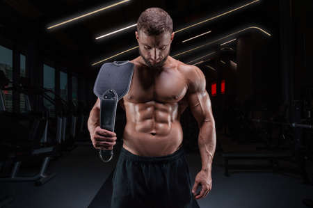 Muscular man posing in the gym with an athletic belt. Fitness concept. Mixed media Фото со стока