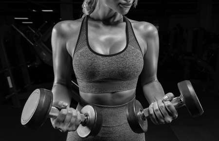 No name portrait of a girl in a tracksuit posing in the gym with dumbbells. Fitness concept. High quality