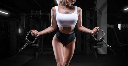 Attractive busty girl working out in a crossover. Fitness and bodybuilding concept. Mixed media Stock fotó