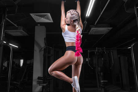 Attractive busty girl pulls herself up on the bar. Fitness and bodybuilding concept. Mixed media Standard-Bild