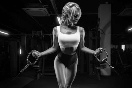 Attractive busty girl working out in a crossover. Fitness and bodybuilding concept. Mixed media