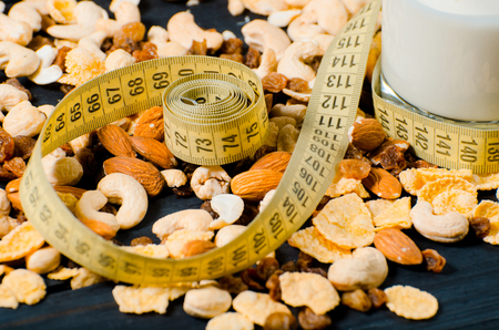 Cereals and centimeter tape is on a wooden background. Healthy lifestyle. Healthy food for weight loss