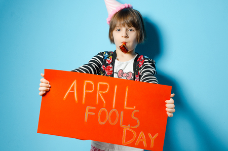 Little girl holding a sheet of paper with the inscription April Fools Day. The holiday is a fools day. The concept of a holiday. Stock Photo