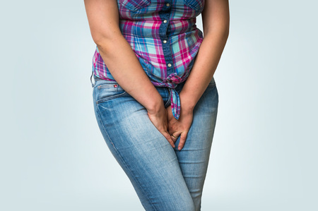 incontinence: Woman with hands holding her crotch, she wants to pee - urinary incontinence concept