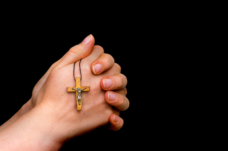 Woman hands holding wooden cross isolated on black background - religion concept