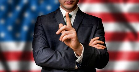 American candidate speaks to the people crowd with one finger on lips - election in United States of America (USA) Stock Photo