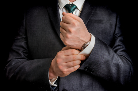 cufflink: Business man fixing his cufflinks - isolated on black background Stock Photo