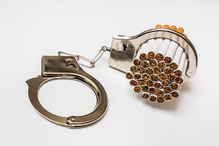 Cigarettes and handcuffs - smoking addiction concept on white background