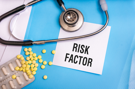 Risk factor words written on medical blue folder with patient files, pills and stethoscope on background Stock Photo