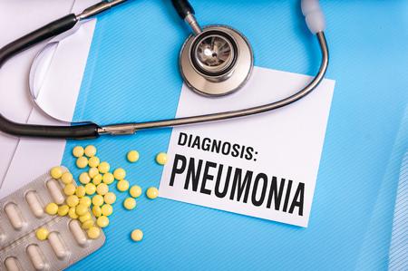 Palabra de neumonía escrita en la carpeta médica azul con archivos de pacientes, píldoras y estetoscopio sobre fondo